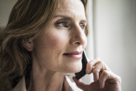 Portrait of smiling mature woman on cell phone - MOEF00790