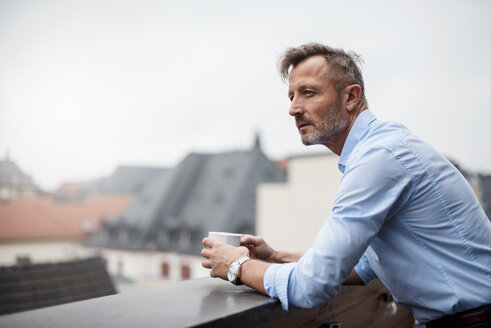 Portrait of mature businessman with cup of coffee on roof terrace - DIGF03280