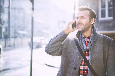 Portrait of smiling man on the phone in winter - BSZF00226