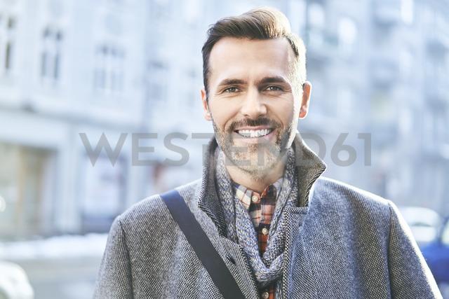 Portrait of smiling man on city street in winter - BSZF00229