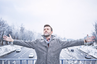 Portrait of man with arms outstretched standing on bridge above motorway - BSZF00232