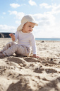 Spain, Lanzarote, baby girl sitting on the beach - DIGF03291