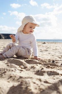 Spain, Lanzarote, baby girl sitting on the beach - DIGF03291
