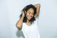 Portrait of happy young woman listening music with headphones - KIJF01901