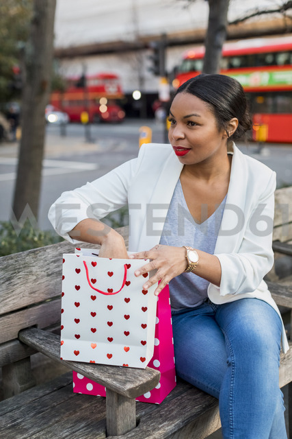 UK, London, woman with shopping bags sitting on a bench in the city - MAUF01343