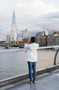 UK, London, woman standing on a bridge taking picture of The Shard - MAUF01346
