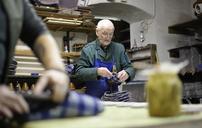 Senior shoemaker working on slippers in workshop - BFRF01818