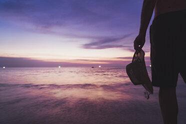 Thailand, Phuket, man standing at seaside by sunset, partial view - KKAF00867