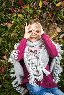 Portrait of smiling girl lying on autumnal meadow looking through her fingers formed like spectacles - SARF03556