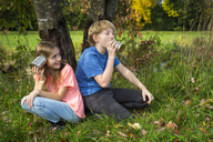 Boy and girl on a meadow having fun with tin can phone - SARF03559