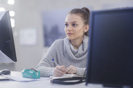 Portrait of young woman working at desk in an office - SGF02174
