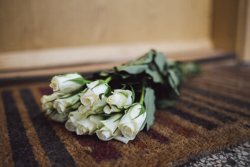 Bunch of white farewell flowers lying on floor mat at apartment door of deceased neighbour - JSCF00057