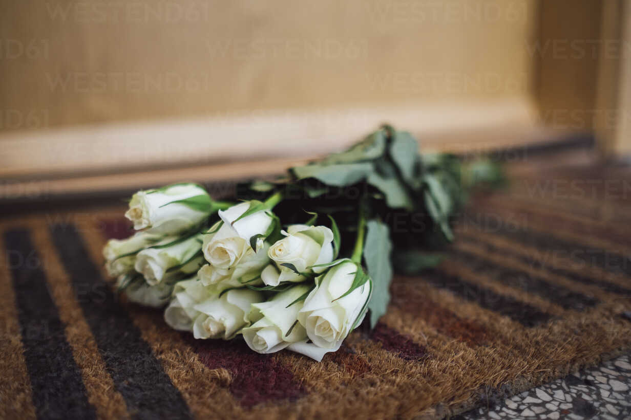Bunch of white farewell flowers lying on floor mat at apartment door of deceased neighbour - JSCF00057 - Jonathan Schöps/Westend61