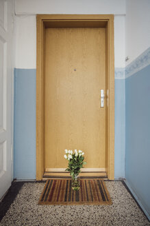 Vase with bunch of white farewell flowers on floor mat at apartment door of deceased neighbour - JSCF00060