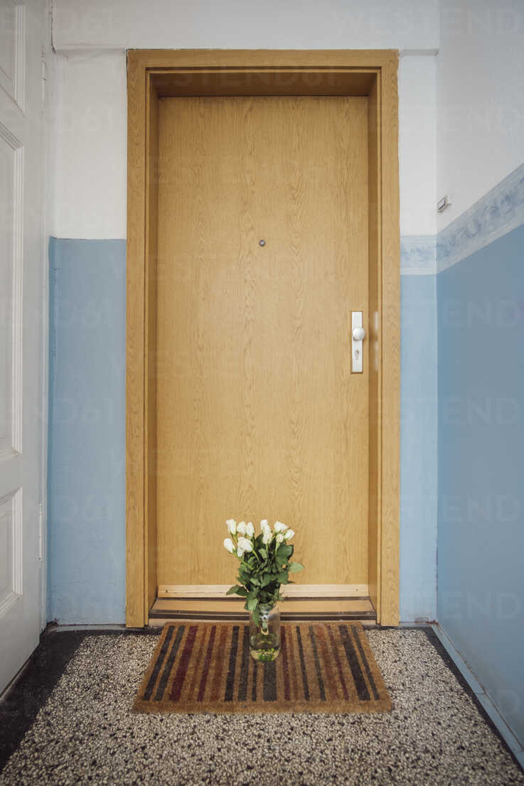 Vase with bunch of white farewell flowers on floor mat at apartment door of deceased neighbour - JSCF00060 - Jonathan Schöps/Westend61