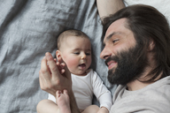 High angle view of affectionate father and baby girl in bed - FSIF00045