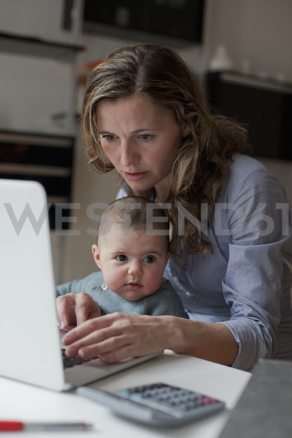 Woman working on laptop while sitting with baby girl at home - FSIF00069 - fStop/Westend61