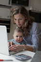 Woman working on laptop while sitting with baby girl at home - FSIF00069