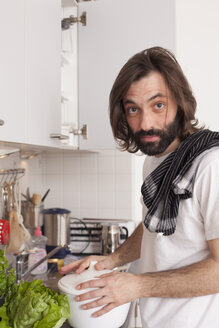 Portrait of man cooking in domestic kitchen - FSIF00072