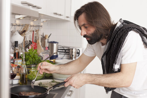 Mid adult man preparing meat in domestic kitchen - FSIF00075