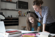 Mother assisting daughter in doing homework at table - FSIF00078