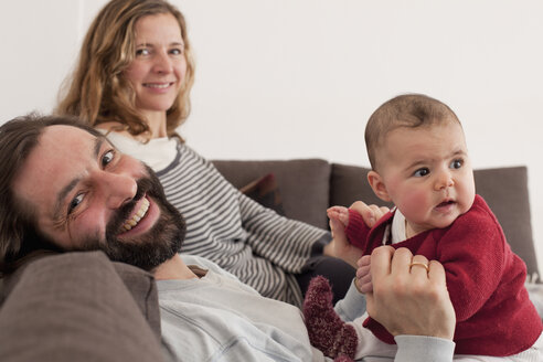 Portrait of happy parents with baby girl on sofa - FSIF00084