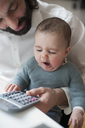 Cute baby girl yawning with father using calculator at home - FSIF00090