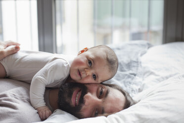 Portrait of loving father with baby girl lying in bed - FSIF00102