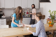 Man looking at family arranging plates on table in kitchen - FSIF00105