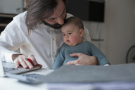 Man looking at baby girl while working at home - FSIF00114