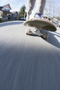 Low section of man skateboarding on road - FSIF00120