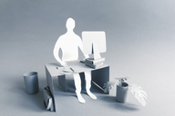Paper businessman working at desk over gray background - FSIF00159