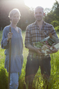 Portrait of mature couple with crate of freshly harvested vegetables at community garden - FSIF00180