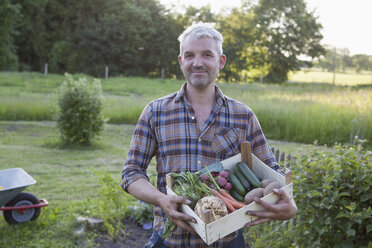 Portrait of smiling mature man carrying crate of freshly harvested vegetables at garden - FSIF00183