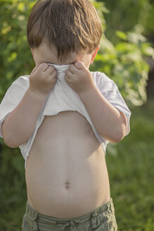 Young boy covering face with t-shirt in park - FSIF00231