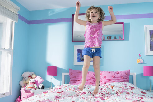 Full length of little girl jumping on bed at home - FSIF00249