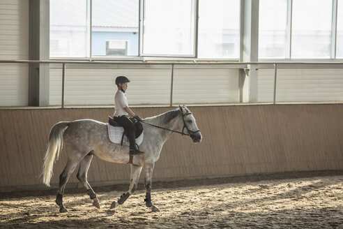 Side view of boy sitting on horse in training stable - FSIF00258