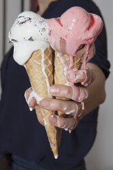 Midsection of senior woman holding melting ice cream cones at home - FSIF00267