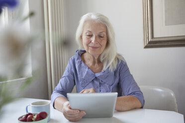 Senior woman using digital tablet at home - FSIF00270