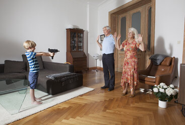 Little boy aiming with toy gun towards grandparents at home - FSIF00273