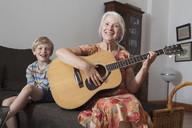 Portrait of boy sitting with grandmother playing guitar on sofa at home - FSIF00276