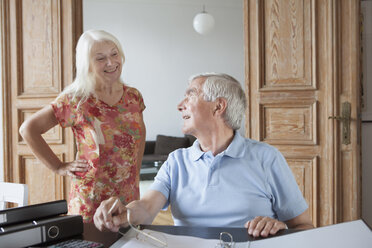Senior man looking at woman while calculating home finance at table - FSIF00279