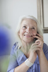 Happy senior woman answering mobile phone at home - FSIF00282