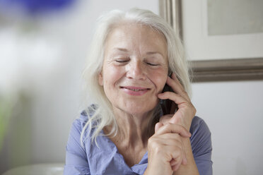 Delightful senior woman answering mobile phone at home - FSIF00285