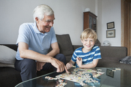 Portrait of happy boy solving jigsaw puzzle with grandfather in living room at home - FSIF00288
