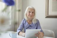 Portrait of confident senior woman holding digital tablet at tablet - FSIF00291