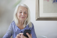 Senior woman text messaging through smart phone at home - FSIF00294