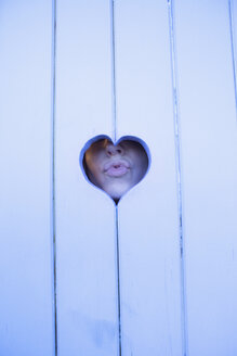 Close-up of woman puckering lips through heart shape wood - FSIF00306