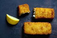 Fish fingers and lemon slice on dark metal - CSF28909