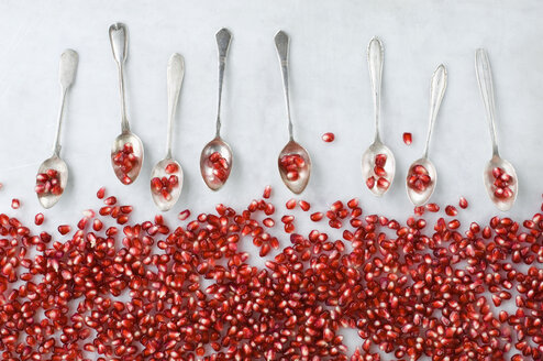 Pomegranate seeds and row of silver tea spoons on white marble - ASF06149